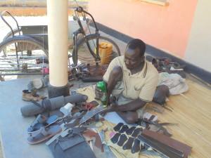 Polio survivor Issa Gabriel received work skills training (shoemaking) from Cheshire Services Uganda