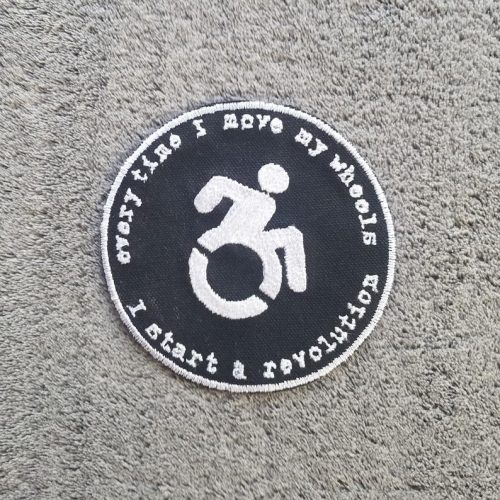 """A round black patch with a wheelchair user in the centre. Around it, the text reads """"when I move my wheels I start a revolution"""""""