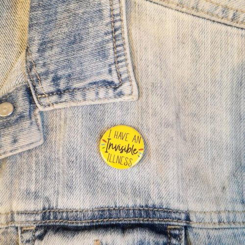 """A denim jacket with a bright yellow badge on it. The badge reads """"I have an invisible illness""""."""