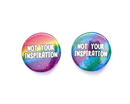 """Two badges on a white background which each say """"not your inspiration"""". The left is a glittery rainbow, while the right is glittery green, blue and purple."""