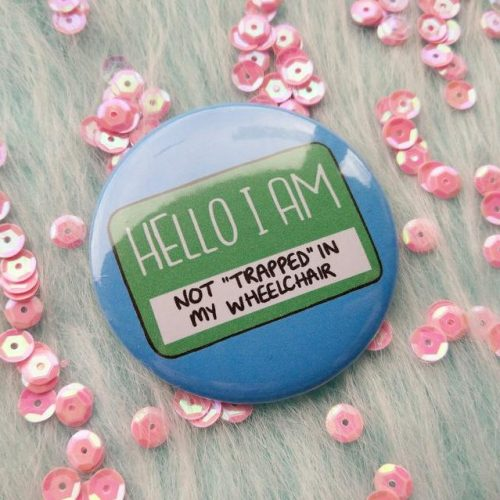 """A badge on a background of sequins. It is blue and features a badge which traditionally tells people their names. This one reads """"Hello I am not """"trapped"""" in my wheelchair"""""""