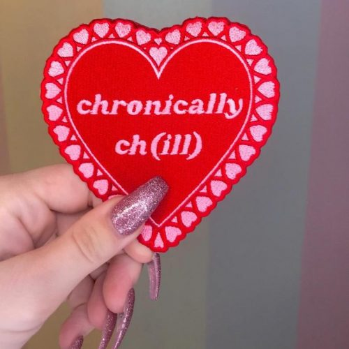 """A heart shaped patch featuring the words """"chronically chill"""""""