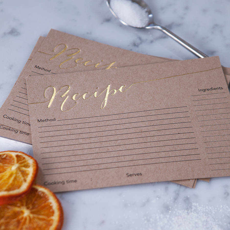 Three brown recipe cards lying on a marble surface. Around them are slices of orange, and a spoonful of sugar.