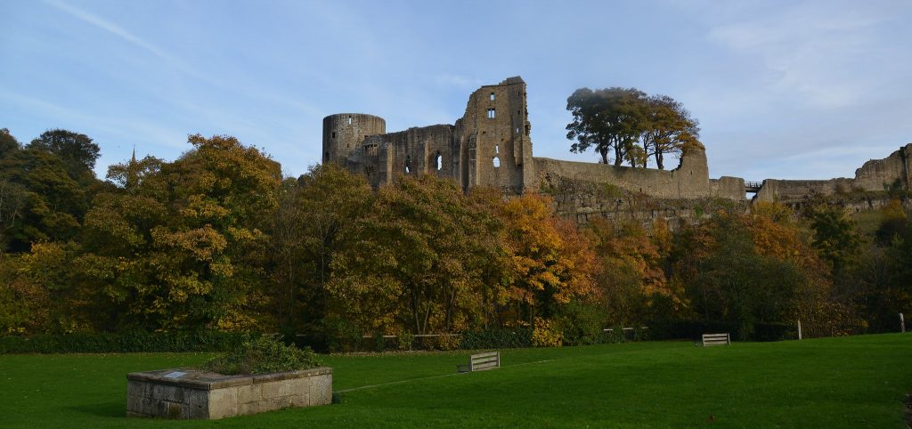 The ruins of Barnard Castle, behind lush, well-maintained grass and trees. A great place to test one's eyesight