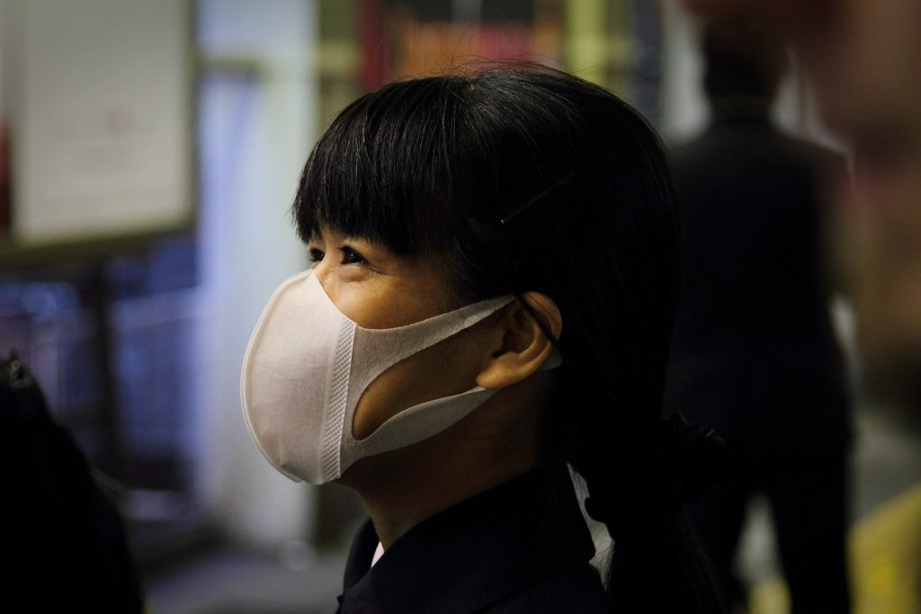 A woman's face in profile, wearing a mask over her mouth and nose, thank goodness