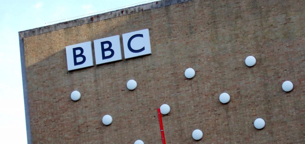 "The BBC's logo on the side of Television Centre, inside which there is presumably a copy of ""How To Win Friends and Influence People"""