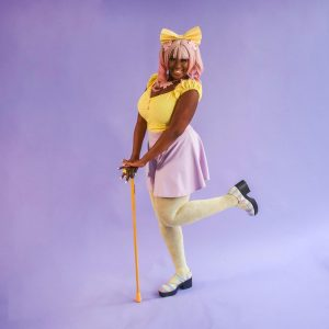 Person in bright clothes posing with her leg popped in the air, supported by her walking stick